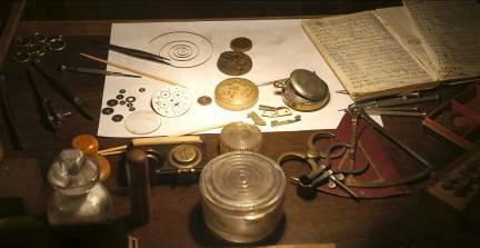 Разобранные часы на столе мастера